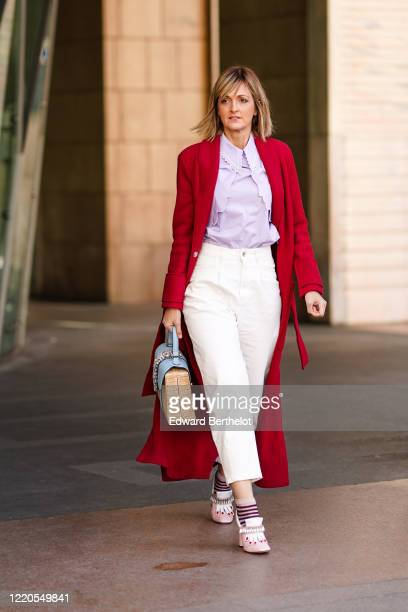 Guest wears a red long jacket, pale purple mauve shirt, white cropped pants, a bag, striped pink socks, shoes, outside Vivetta, during Milan Fashion...
