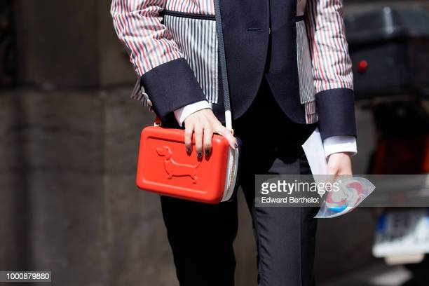 A guest wears a red plastic rigid bag depecting a dog outside Thom Browne during Paris Fashion Week Menswear SpringSummer 2019 on June 23 2018 in...