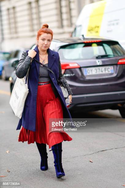 A guest wears a red pleated skirt a purple jacket a gray top blue boots has red hair outside Leonard during Paris Fashion Week Womenswear...