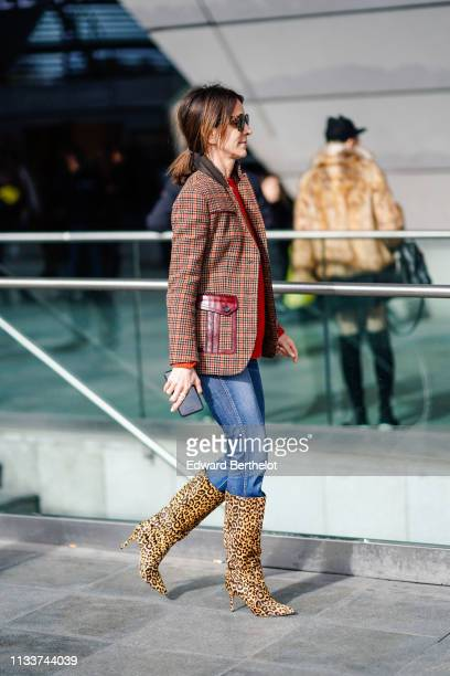 A guest wears a red Prince of Wales check jacket blue jeans yellow leopard print boots outside Giambattista Valli during Paris Fashion Week...