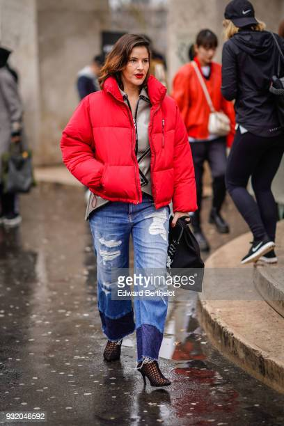 Guest wears a red puffer, a lustrous beige zip front asymmetric jacket, a black shopping bag, ripped blue jeans with navy blue ends, black fishnet...