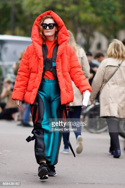 A guest wears a red puffer coat with a hood blue and black pants black sneakers outside Valentin Yudashkin during Paris Fashion Week Womenswear...