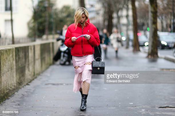 A guest wears a red puffer jacket a pink skirt fishnet tights black leather boots and a black bag outside the Valentin Yudashkin show during Paris...