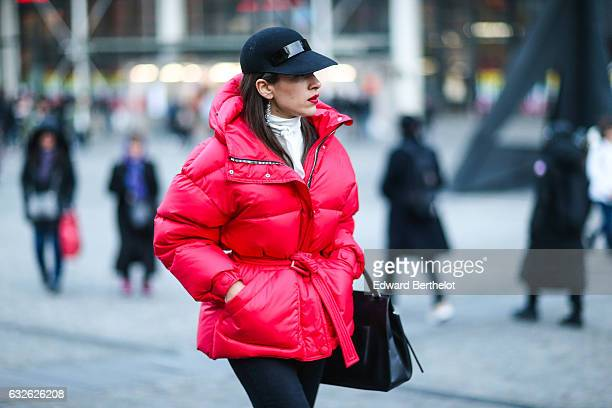 A guest wears a red puffer jacket and a cap outside the Vetements show at Centre Pompidou during Paris Fashion Week Haute Couture Spring Summer 2017...