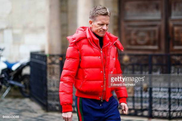 A guest wears a red puffer jacket and Gucci pants outside Thom Browne during Paris Fashion Week Menswear Fall Winter 20182019 on January 20 2018 in...
