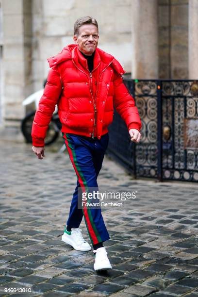 A guest wears a red puffer jacket Gucci pants white sneakers outside Thom Browne during Paris Fashion Week Menswear Fall Winter 20182019 on January...