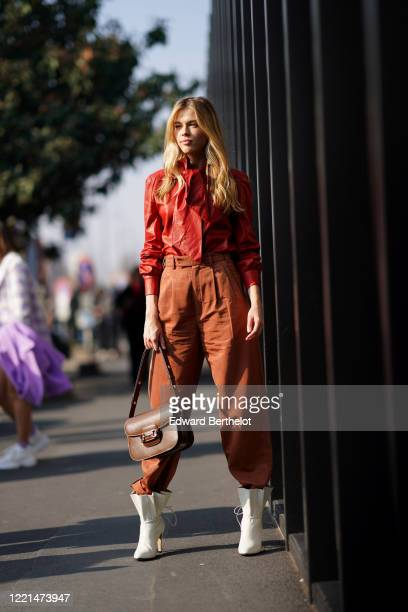 Guest wears a red shiny leather shirt, a brown leather bag, brown pants, white boots, outside Gucci, during Milan Fashion Week Fall/Winter 2020-2021,...