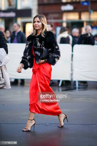 A guest wears a red silky dress high heels shoes a fluffy fur coat outside the Opera Garnier 350th Anniversary Gala in Paris on May 08 2019 in Paris...