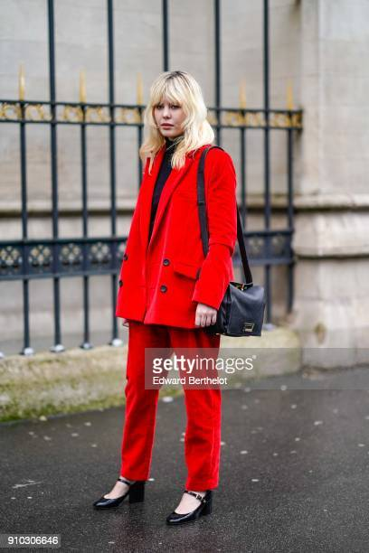 A guest wears a red suit blazer jacket a black bag outside Maison Rabih Kayrouz during Paris Fashion Week Haute Couture Spring/Summer 2018 on January...