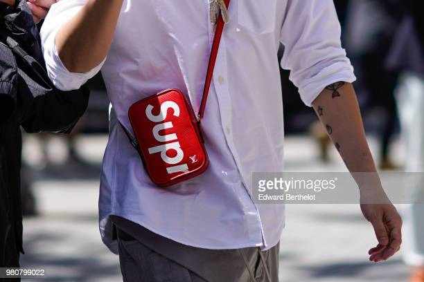A guest wears a red Supreme mini bag outside Louis Vuitton during Paris Fashion Week Menswear SpringSummer 2019 on June 21 2018 in Paris France