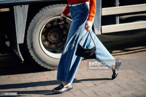 A guest wears a red sweater a white belt blue wide leg denim pants black moccasins a black bag during London Fashion Week February 2019 on February...