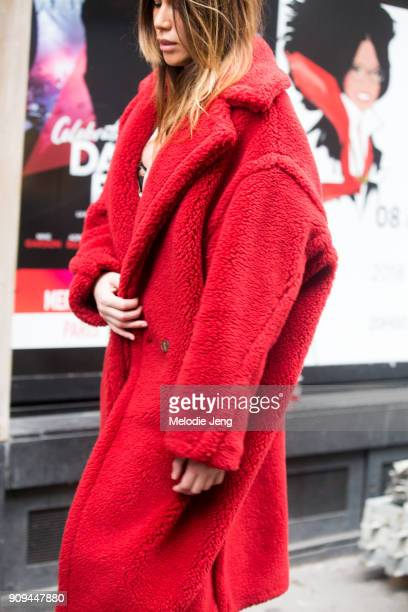 A guest wears a red teddy bear coat outside the Alexis Mabille show at Salle Pleyel on January 23 2018 in Paris France