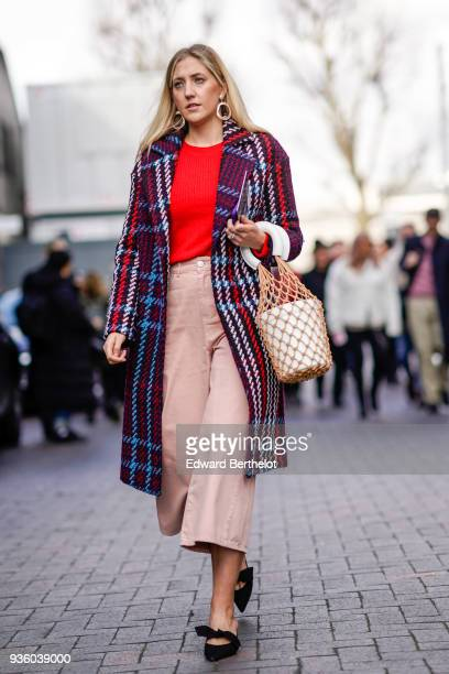 A guest wears a red top a checked coat cropped pink pants a basket bag during London Fashion Week February 2018 on February 18 2018 in London England