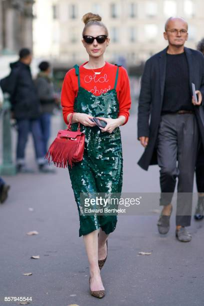A guest wears a red top a green dress sunglzsses a red bag with fringes outside Thom Browne during Paris Fashion Week Womenswear Spring/Summer 2018...