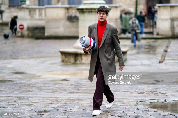 A guest wears a red turtleneck pull over a coat flare pants white sneakers shoes outside Thom Browne during Paris Fashion Week Menswear Fall Winter...