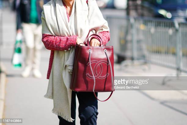 A guest wears a red tweed jacket a Chanel ring a cream color scarf a red studded Chanel bag outside the Chanel Cruise Collection 2020 At Grand Palais...