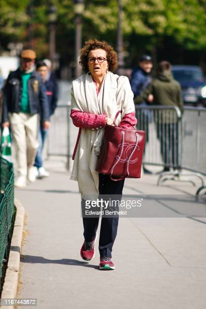 A guest wears a red tweed jacket a Chanel ring a cream color scarf a red studded Chanel bag black pants red sneakers outside the Chanel Cruise...