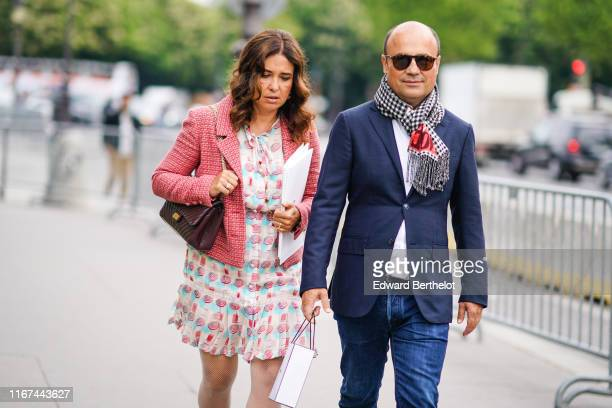 A guest wears a red tweed jacket a colorful geometric design dress a brown Chanel bag A guest wears sunglasses a black white and red checkered scarf...