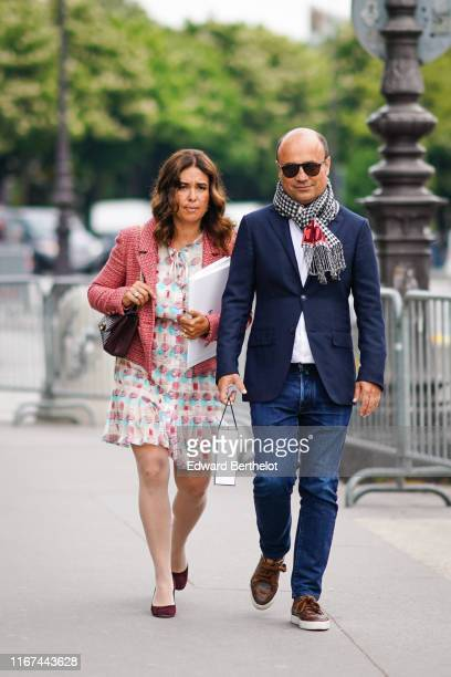 A guest wears a red tweed jacket a colorful geometric design dress a brown Chanel bag burgundy suede shoes A guest wears sunglasses a black white and...