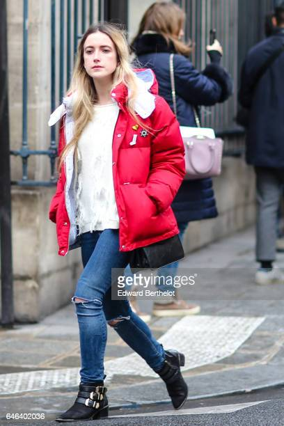 A guest wears a red winter puffer coat a white top blue denim ripped jeans pants and black boots outside the JOUR/NE show during Paris Fashion Week...
