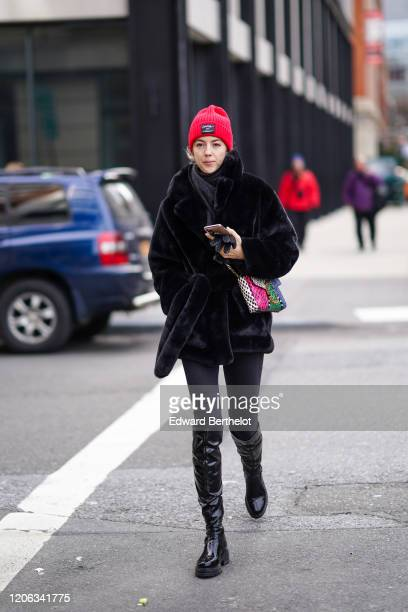 A guest wears a red wool beanie hat a fluffy coat black pants black shiny boots a colored bag during New York Fashion Week Fall Winter 2020 on...