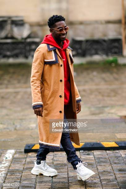 A guest wears a redd hoodie sweater an orange coat white sneakers outside Thom Browne during Paris Fashion Week Menswear Fall Winter 20182019 on...
