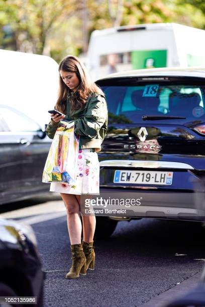 A guest wears a reen bomber jacket and a wite floral print dress suede boots outside Haider Ackermann during Paris Fashion Week Womenswear...