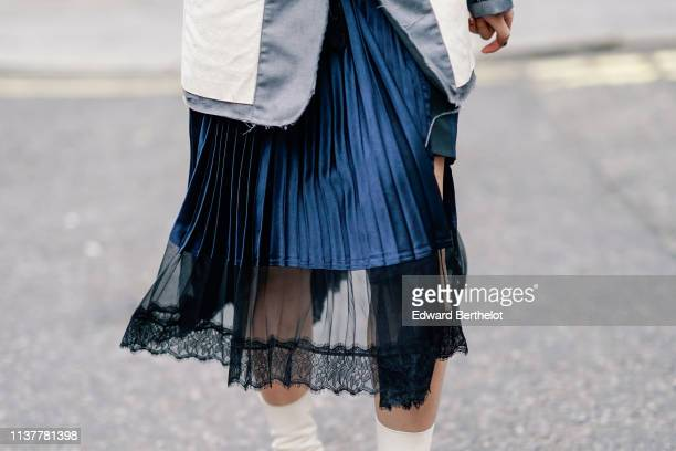 A guest wears a ripped hem grey jacket with white inserts a shiny dark blue pleated satin and lace lingerie skirt during London Fashion Week February...