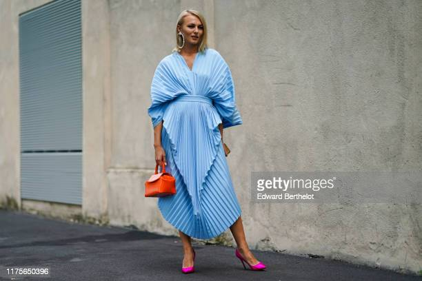 A guest wears a ruffled and pleated blue dress an orange bag neon pink shoes large earrings outside the Prada show during Milan Fashion Week...