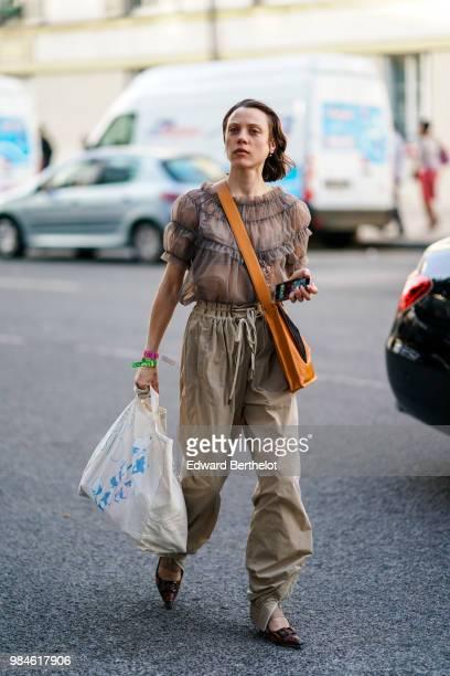 A guest wears a ruffled mesh top beige pants brown shoes outside 1017 ALYX 9SM during Paris Fashion Week Menswear SpringSummer 2019 on June 24 2018...
