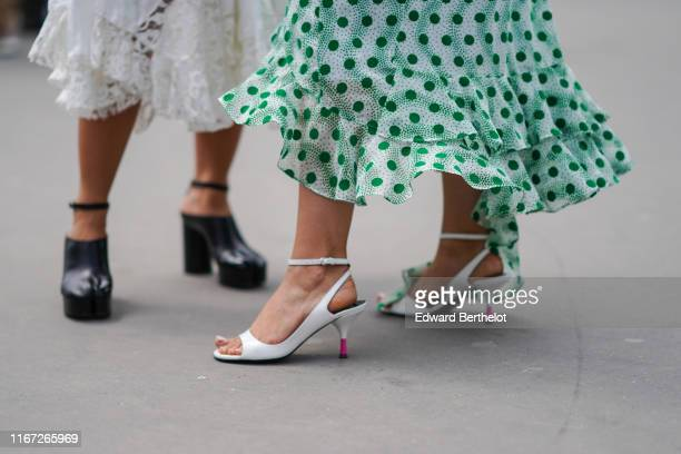 Guest wears a ruffled skirt with green polka dots, white slingback ankle-strap pumps, outside Kenzo, during Paris Fashion Week - Menswear...
