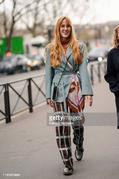 A guest wears a rustcolor turtleneck a light green jacket brown and light green checkered pants shiny silver shoes outside Redemption during Paris...