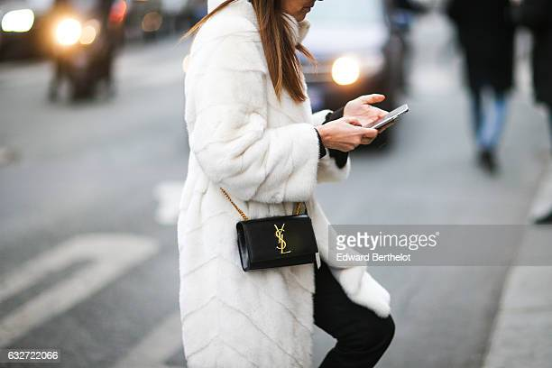 A guest wears a Saint Laurent YSL bag and a white fur coat outside the Jean Paul Gaultier show during Paris Fashion Week Haute Couture Spring Summer...