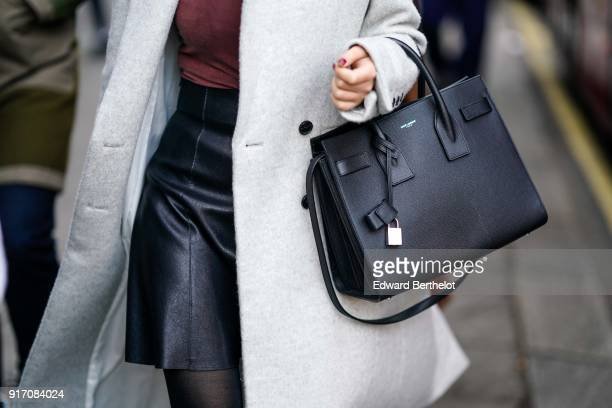 A guest wears a Saint Laurent YSL bag during London Fashion Week Men's January 2018 at on January 6 2018 in London England