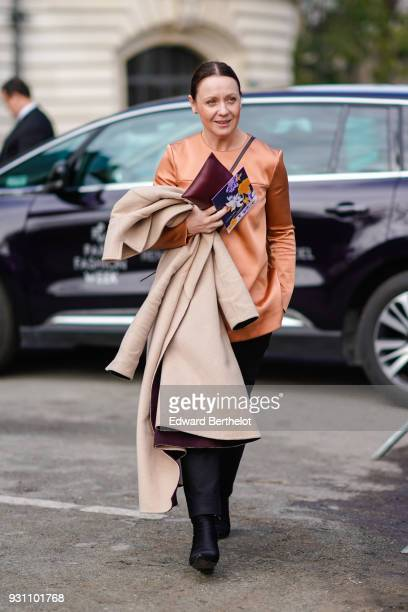 A guest wears a salmon tunic a beige coat black boots during Paris Fashion Week Womenswear Fall/Winter 2018/2019 on March 5 2018 in Paris France