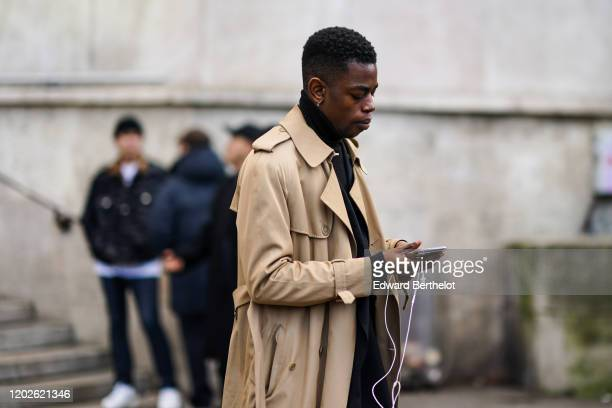 Guest wears a sand color trench coat, during Paris Fashion Week - Menswear Fall/Winter 2020-2021 on January 19, 2020 in Paris, France.