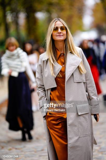 A guest wears a satin orange dress and a gray trench coat outside Beautiful People during Paris Fashion Week Womenswear Spring/Summer 2019 on October...