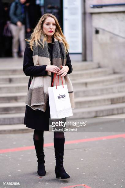 A guest wears a scarf a black coat tights black thigh high boots outside Junko Shimada during Paris Fashion Week Womenswear Fall/Winter 2018/2019 on...