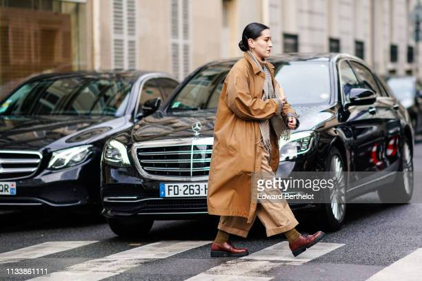 A guest wears a scarf a camel trench coat beige wideleg pants brown shoes outside APC during Paris Fashion Week Womenswear Fall/Winter 2019/2020 on...