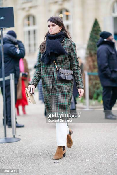 A guest wears a scarf a checked coat a black bag white pants brown suede boots during Paris Fashion Week Womenswear Fall/Winter 2018/2019 on February...