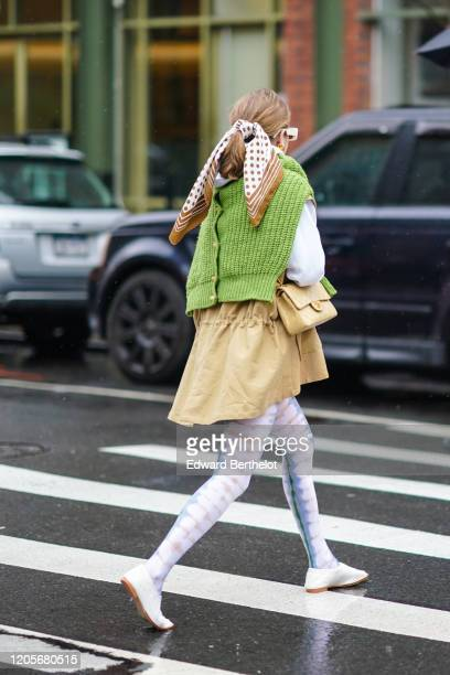 A guest wears a scarf attached to the hair a green wool pullover over the shoulders a VChanel bag a beige skirt leggings white shoes during New York...