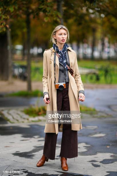 Guest wears a scarf over the head, a beige long coat, a gray vest, brown flared pants, brown leather pointy boots, a crossbody bag, a Fuji compact...