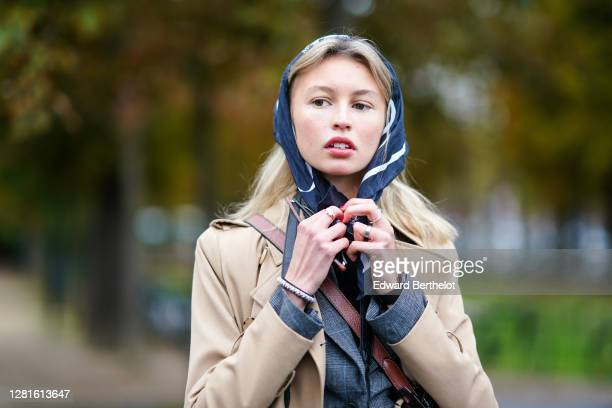 Guest wears a scarf over the head, a beige long coat, a gray vest, outside Chanel, during Paris Fashion Week - Womenswear Spring Summer 2021, on...
