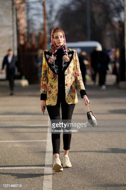 Guest wears a scarf over the head, a floral print yellow jacket, black leggings, a bag, sneakers, outside Alberta Ferretti, during Milan Fashion Week...