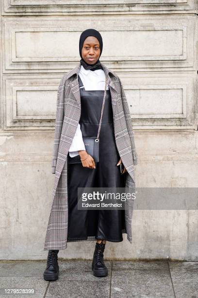 Guest wears a scarf over the head, a gray long checked coat, a white shirt, a black leather dress, black leather boots, a bag, outside Louis Vuitton,...
