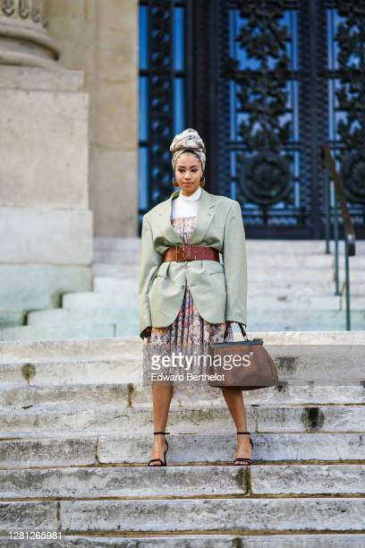 Guest wears a scarf over the head, a pale green oversized blazer jacket, a large brown leather belt, a floral print pleated skirt, a brown large bag,...