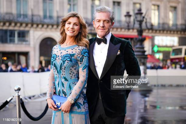A guest wears a seethrough embroidered blue muslin dress a blue Hermes crocodile pattern clutch A guest wears a white shirt a black bowtie a black...