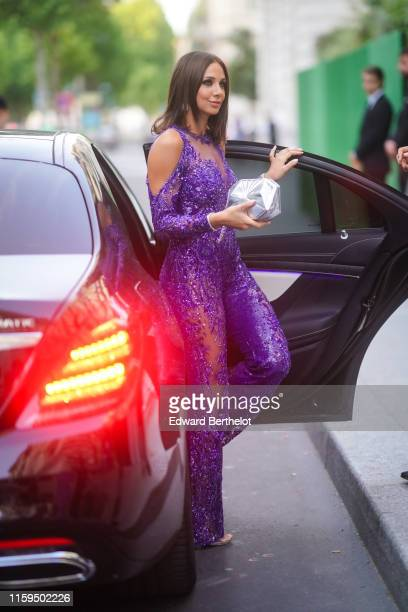 A guest wears a sequined and beaded transparent purple muslin coldshoulder jumpsuit a shiny silver Chanel clutch outside AMFAR dinner during Paris...