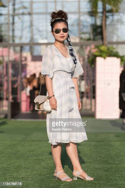 A guest wears a sheer blue chiffon dress headscarf and sunglasses at Melbourne Fashion Festival on March 9 2019 in Melbourne Australia