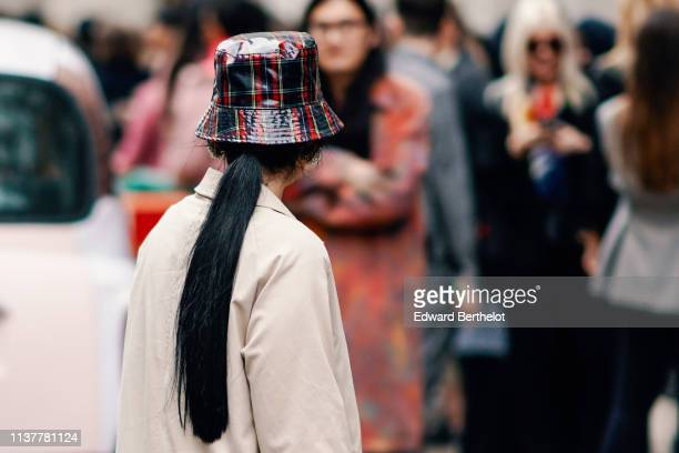 A guest wears a shiny black and red tartan vinyl rain hat during London Fashion Week February 2019 on February 16 2019 in London England